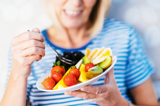 Attractive senior woman with fruit lunch stock photo