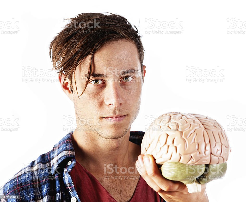Attractive serious young nerd holds model brain royalty-free stock photo