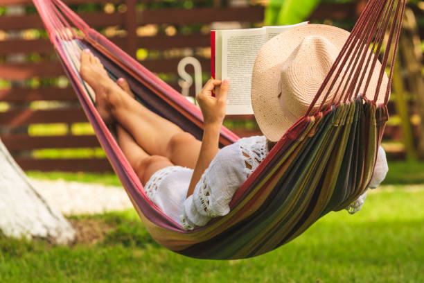 Attractive sexy woman reading book in hammock. stock photo