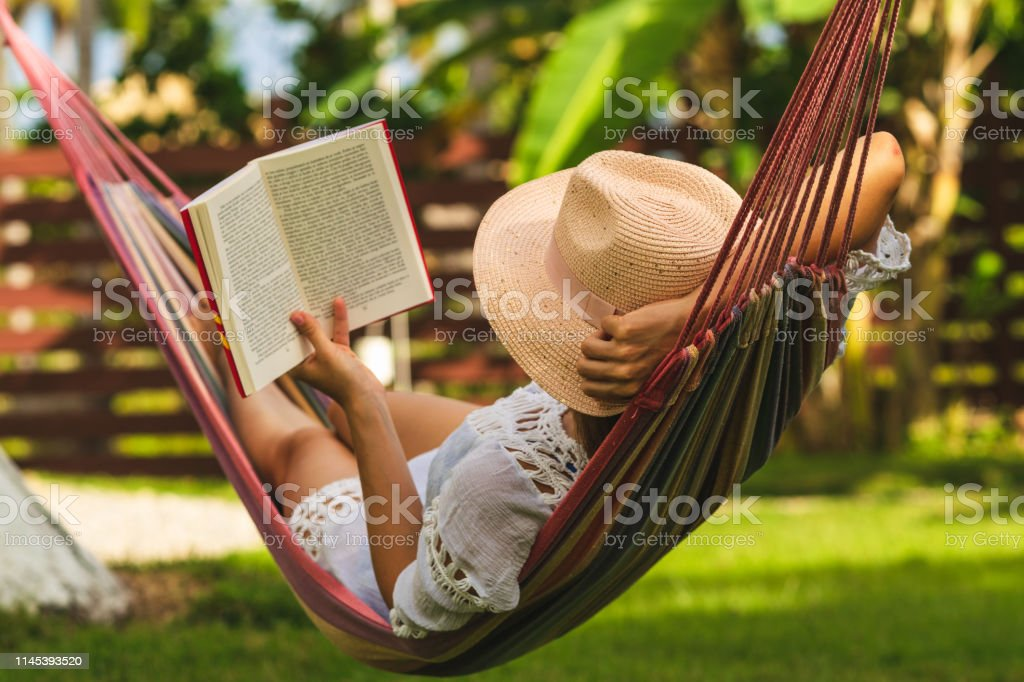 Attractive sexy woman reading book in hammock. Happy beautiful woman in white dress relaxing in hammock. Adult Stock Photo