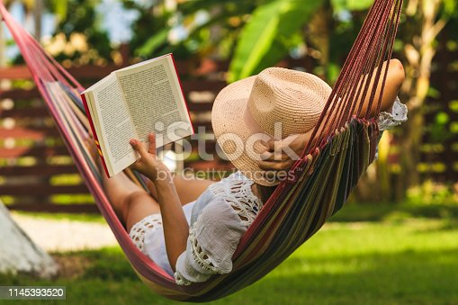Happy beautiful woman in white dress relaxing in hammock.