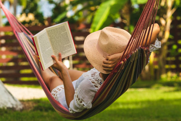 attractive sexy woman reading book in hammock. - backyard stock pictures, royalty-free photos & images
