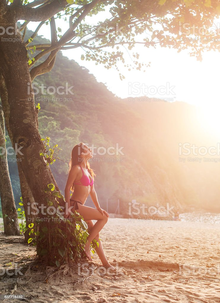 Attractive slim female tourist in bikini leaning against tree with stock photo