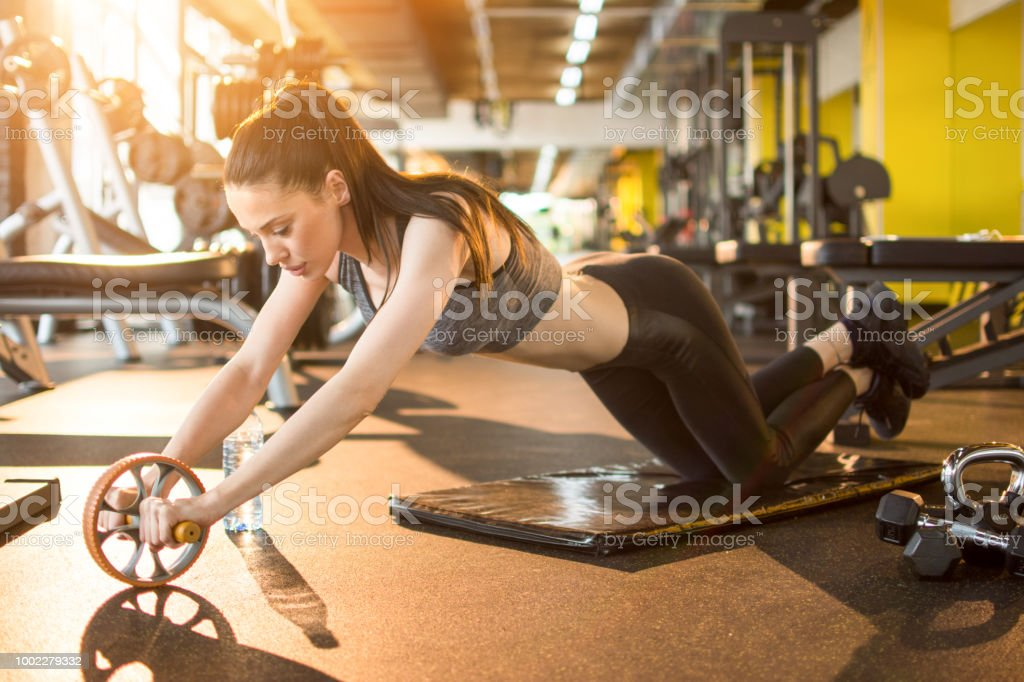 Attractive slim sportswoman workout with abdominal roller in gym stock photo
