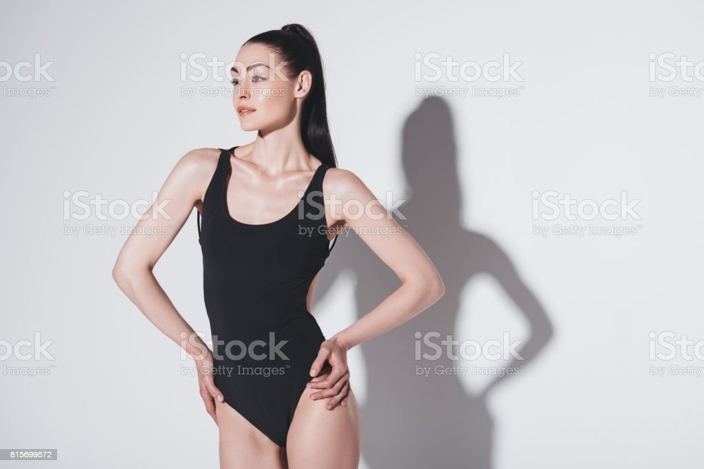 Attractive slim woman in black leotard posing with hands on waist and looking away stock photo
