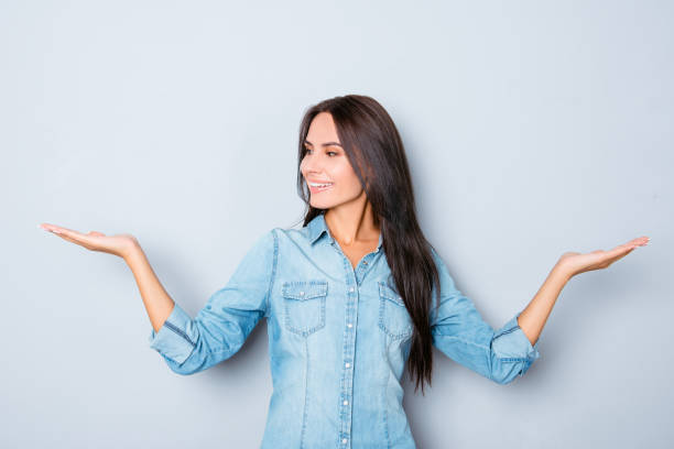 attractive smiling brunette woman showing balance with hands - choosing stock photos and pictures