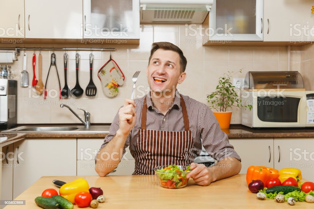 Attractive smiling caucasian young man in apron, brown shirt sitting at table with vegetable salad in bowl, eating in light kitchen. Dieting concept. Healthy lifestyle. Cooking at home. Prepare food. stock photo