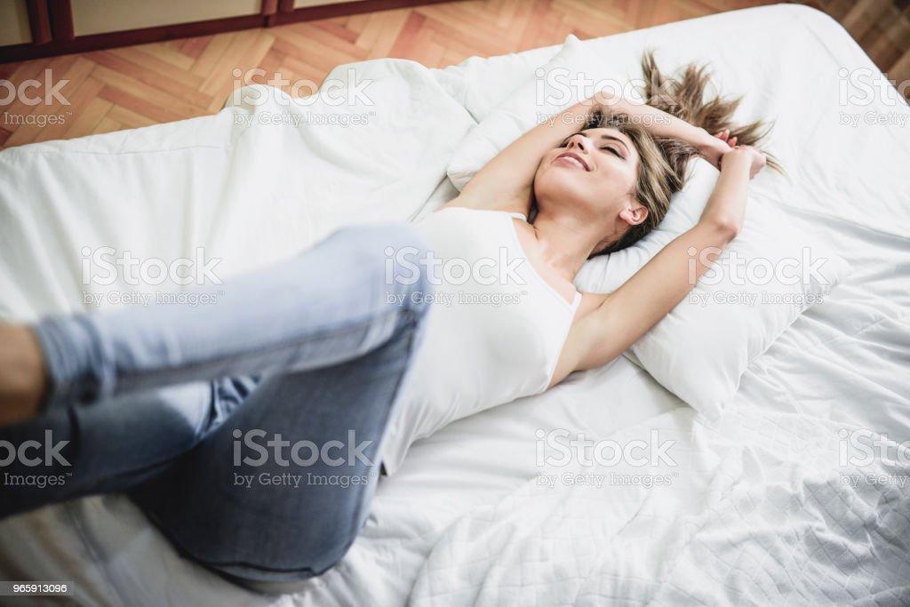 Aantrekkelijke lachende vrouw Waking Up In haar slaapkamer - Royalty-free Alleen volwassenen Stockfoto
