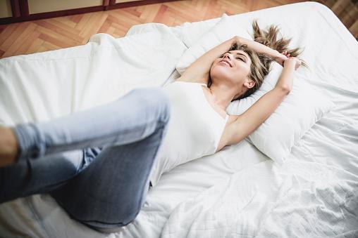Aantrekkelijke Lachende Vrouw Waking Up In Haar Slaapkamer Stockfoto en meer beelden van Alleen volwassenen