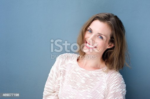 istock Attractive smiling mid adult woman on blue background 469077198
