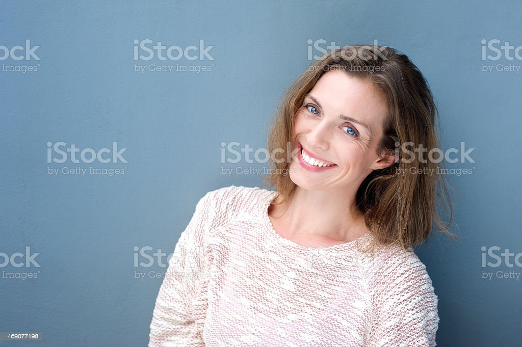 Attractive smiling mid adult woman on blue background stock photo