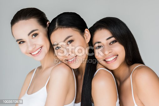 attractive smiling multiethnic women looking at camera isolated on gray background
