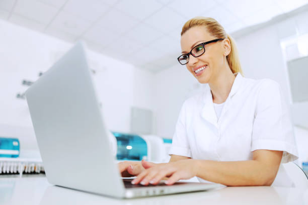 Attractive smiling positive blond lab assistant sitting in laboratory and processing data. stock photo