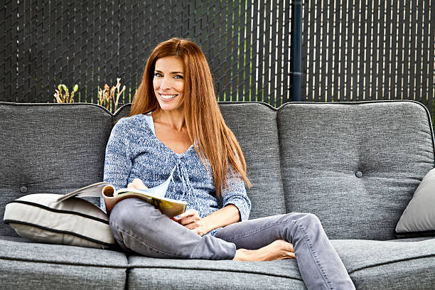 Attractive Smiling Woman Reading In The Backyard stock photo