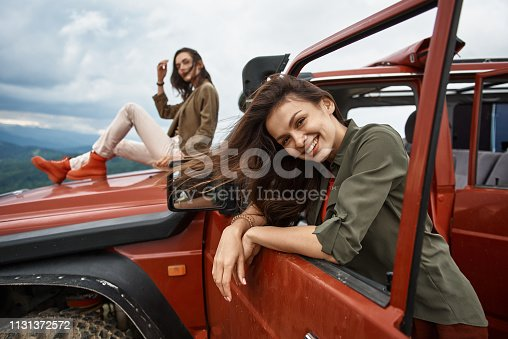 1131372580 istock photo Attractive smiling woman using her off-road car 1131372572