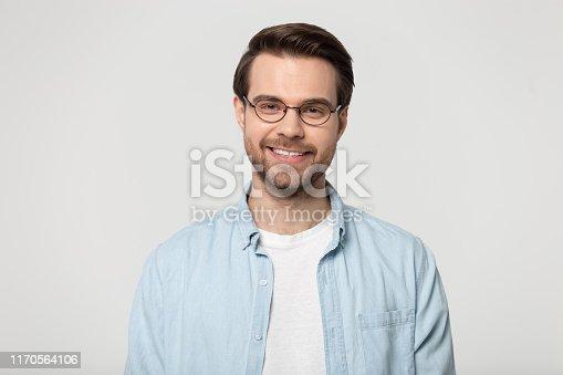 istock Attractive smiling young man in glasses studio headshot 1170564106