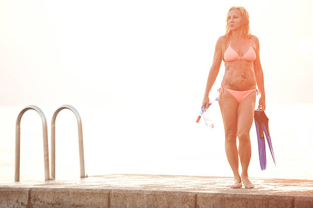 Attractive Snorkel Woman after Diving on a Pier Attractive Snorkel Woman after Diving standing on a Pier. Mature slim woman has long blond hair and wearing pink bikini. Back lit. Horizontal color image. middle aged women in bikinis stock pictures, royalty-free photos & images