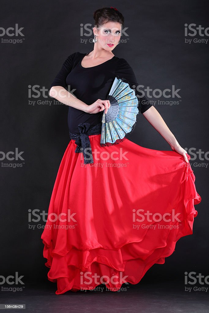 Attractive spanish young woman dancing flamenco over black backg royalty-free stock photo