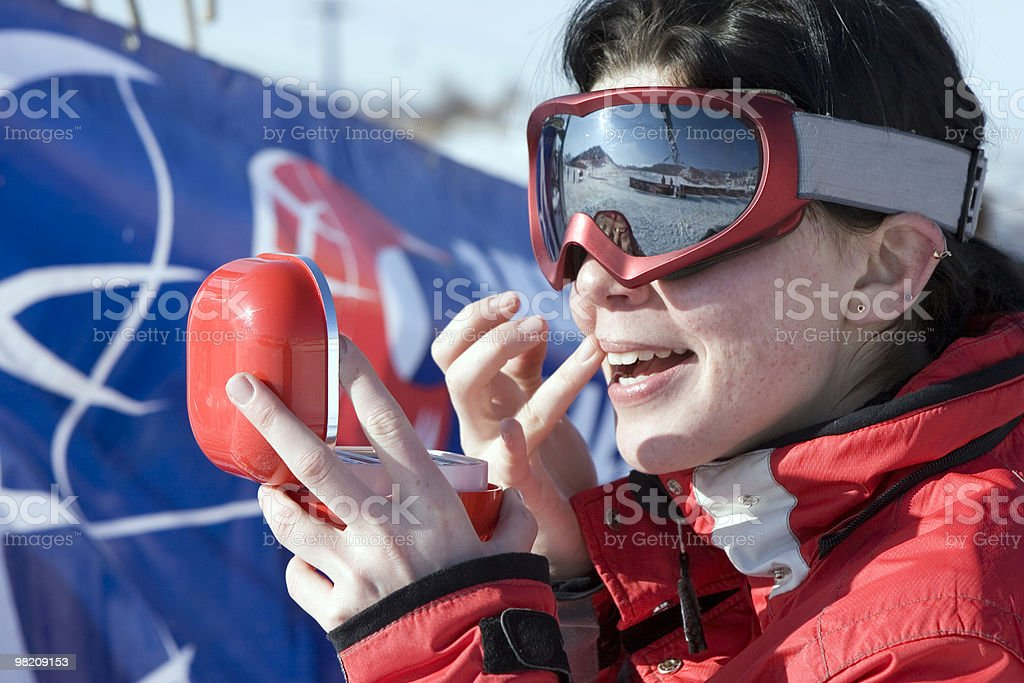 Attractive sport girl snowboarder applying face pack outdoors in mountain stock photo