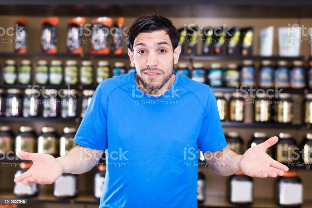 attractive sportman standing in sport nutrition store stock photo