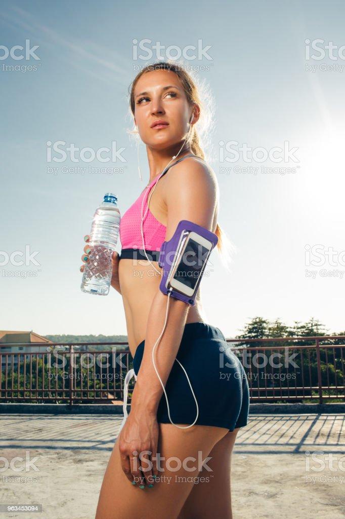 Kulaklıklar içinde çekici sporcumuz ile çalışan çatı su şişe tutan çantası içinde smartphone - Royalty-free Aktivite Stok görsel