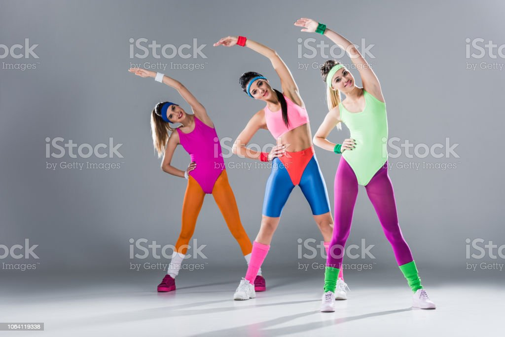 attractive sporty girls in bodysuits training at aerobics workout on grey royalty-free stock photo