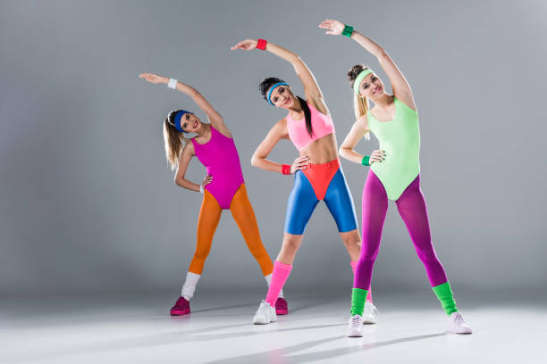 attractive sporty girls in bodysuits training at aerobics workout on grey - aerobics stock photos and pictures