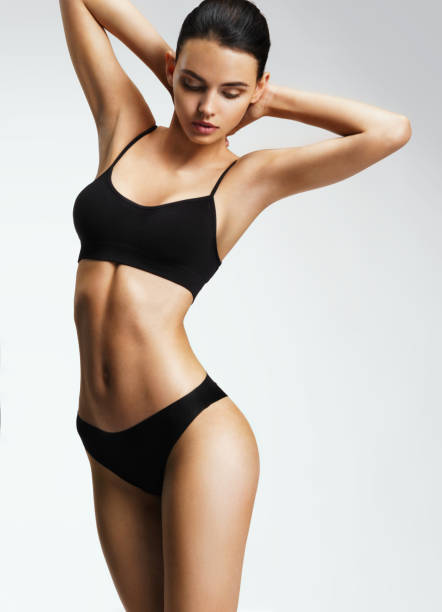 Attractive sporty woman in black bikini posing on grey background. Attractive sporty woman in black bikini posing on grey background. Photo of brunette woman with slim toned body. Beauty and body care concept bikini stock pictures, royalty-free photos & images