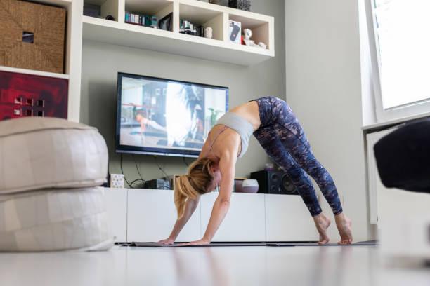 Atractiva mujer deportiva haciendo ejercicio en casa, haciendo ejercicio de pilates frente a la televisión en su sala de estar. Distancia social. Manténgase saludable y permanezca en casa durante la pandemia del virus coronario - foto de stock