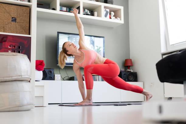 Attraktive sportliche Frau trainieren zu Hause, pilates Bewegung vor dem Fernseher in ihrem Wohnzimmer. Soziale Entsung. Bleiben Sie gesund und bleiben Sie zu Hause während der Corona-Virus-Pandemie – Foto