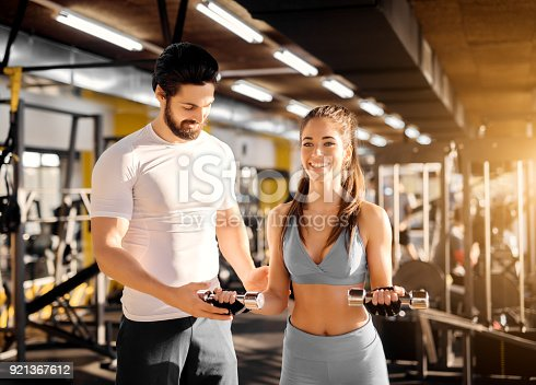 istock Attractive strong muscular trainer showing biceps exercise with little dumbbells to an adorable smiling girl in the gym. 921367612