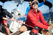 Attractive strong woman sailing with her sail boat