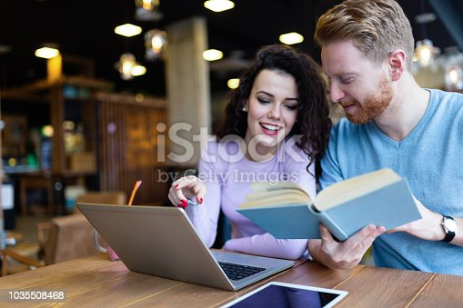 istock Attractive students learning together in coffee shop 1035508468