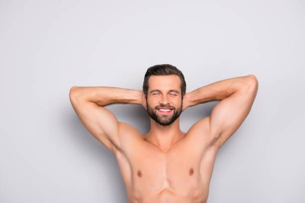 Attrayant, étourdissement, viril, souriant macho isolé sur fond gris, ayant les deux bras derrière le tête et fermé les yeux, montrant ses aisselles rasées - wellness, la notion de bien-être - Photo