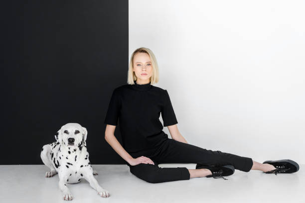 attractive stylish blonde woman in black clothes sitting near black and white wall with dalmatian dog - carnivora stock photos and pictures