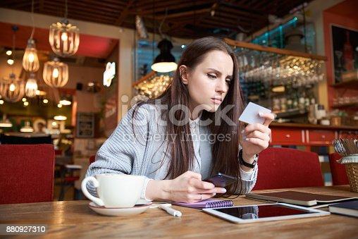 istock attractive stylish modern young woman who is shopping in the Internet sitting at a table in a cafe or bar with your smartphone and makes payment with a Bank card 880927310