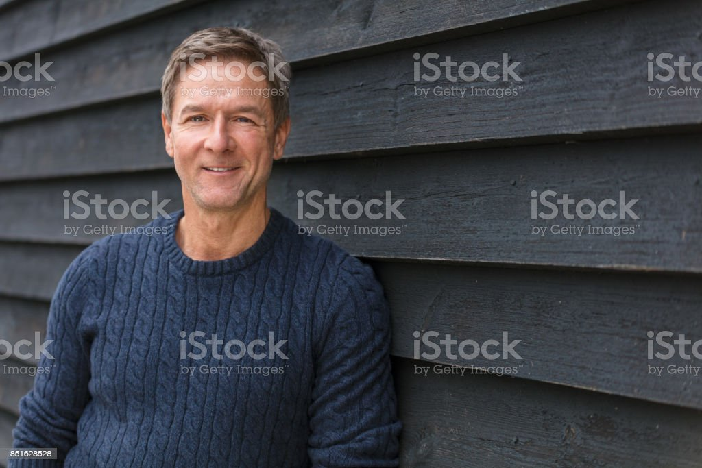 Attractive, successful and happy smiling middle aged man male outside wearing a blue sweater stock photo