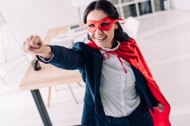 attraktives super geschäftsfrau in cape und maske stehend mit hand im büro - damen umhänge stock-fotos und bilder