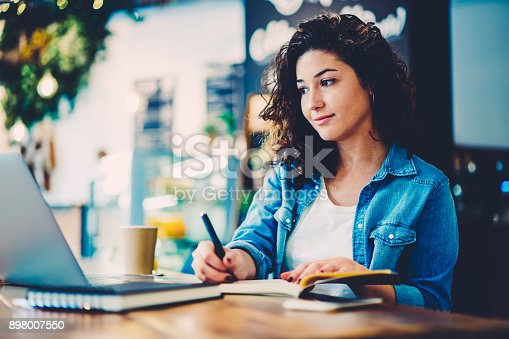 Attractive talented student watching useful training webinar in website and make some notations to notepad sitting in cafe.Hipster girl reading news in webpage on laptop and recording information