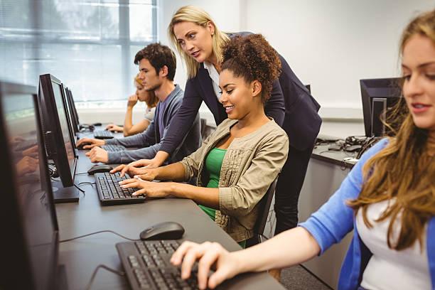 hübsche lehrer helfen ihren student mit computer-klasse - möbel 24 online stock-fotos und bilder