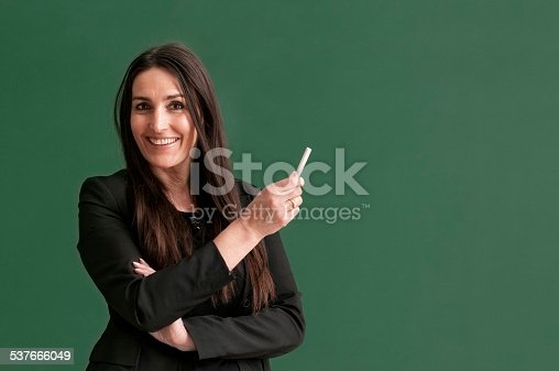 istock attractive teacher with long hair standing at blackboard 537666049