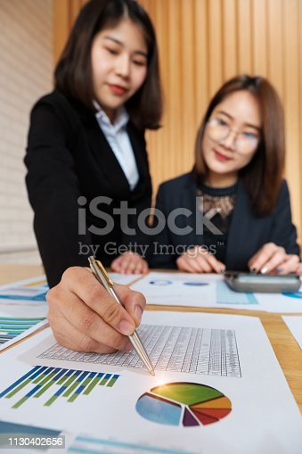istock Attractive teamwork hand holding pen and pointing at financial paperwork in co-working space. 1130402656