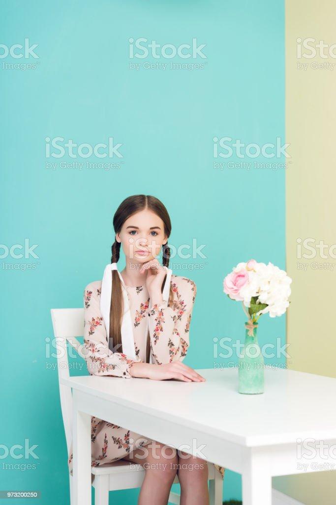 menina adolescente atraente com tranças com vestido de verão, sentado à mesa com flores, em azul - foto de acervo