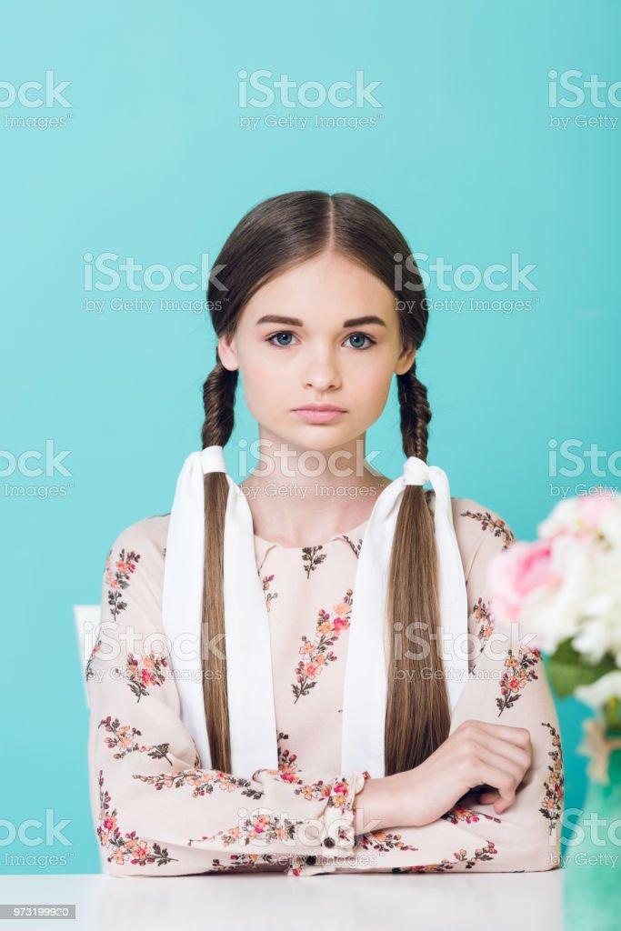 menina adolescente atraente com tranças sentado a mesa com flores, isoladas em azul - foto de acervo