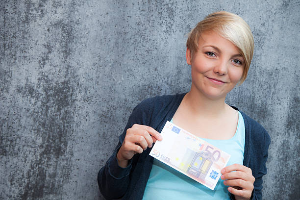 Attractive teenage girl holding fifty euro note Attractive teenage girl holding fifty euro note fifty euro banknote stock pictures, royalty-free photos & images