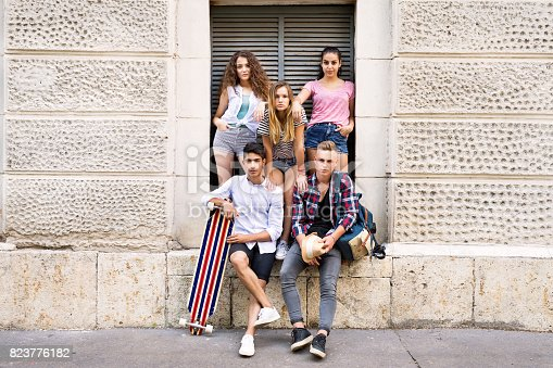824257318 istock photo Attractive teenage students posing in front of university. 823776182