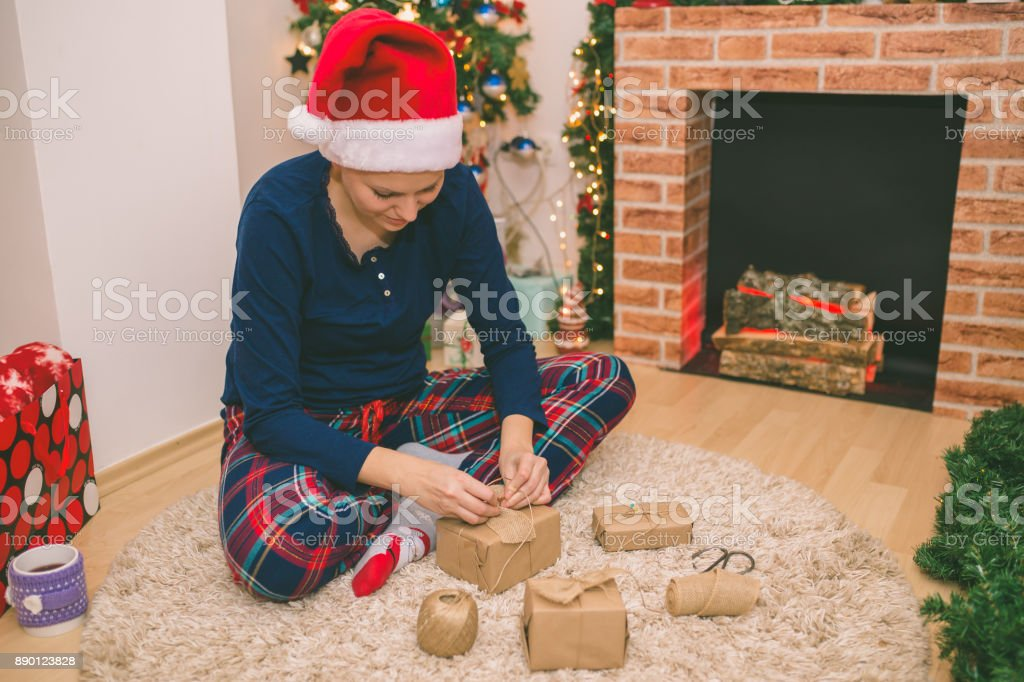 Attractive trendy young woman Christmas with her dog sitting in front of the decorated fireplace and tree patting it on the head with a happy smile. stock photo