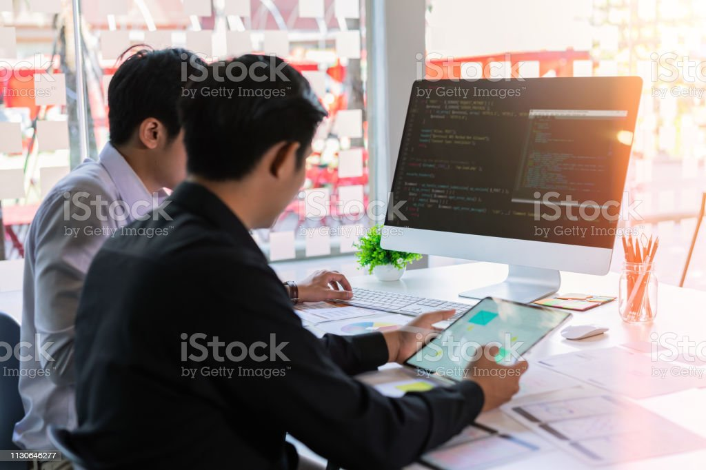 Attractive two young programmers team developing programming and coding mobile responsive website on desktop computer. royalty-free stock photo