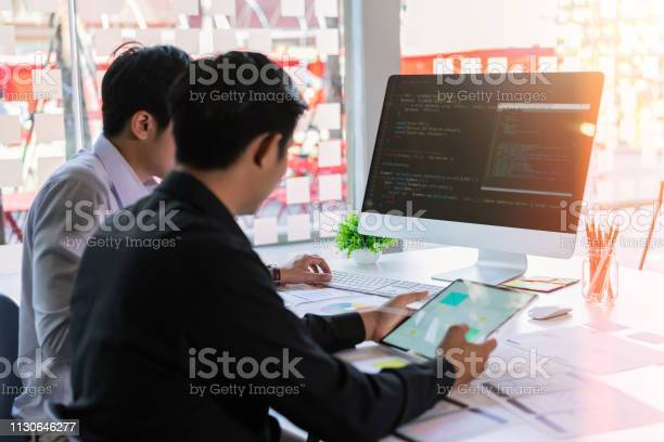 Attractive Two Young Programmers Team Developing Programming And Coding Mobile Responsive Website On Desktop Computer Stock Photo - Download Image Now