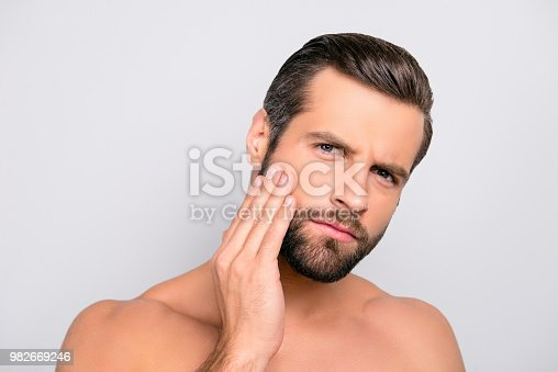 istock Attractive, unhappy, displeased, harsh, virile macho having problem with face, holding hand on cheek, he needs lotion, cream, mask to make soft, smooth, clear, clean skin, isolated on gray background 982669246